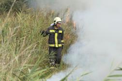 Égő árokpart mellett a tűzoltó