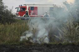 Füstölgő árokpart fölött tűzoltóautó tűzoltókkal