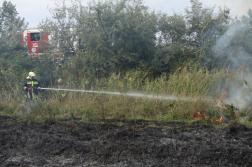 Vízzel oltja az árokpartot a tűzoltó