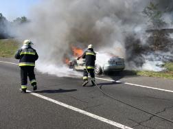 Vízsugárral oltják az égő autót a tűzoltók