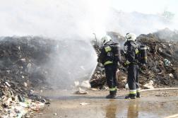 Szemétrakat előtt tűzoltók vízsugárral