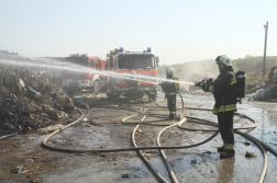Vízsugárral olt a tűzoltó mögötte tűzoltóautók