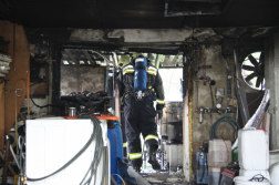 Kiégett melléképület a háttérben tűzoltóval