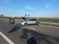 Tűzoltók és az úton keresztbe fordult autó oldalról