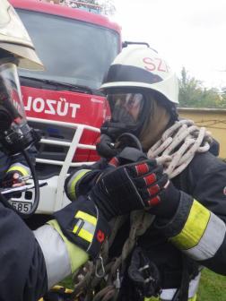 Tűzoltó teljes védőfelszerelésben egy másik tűzoltóval