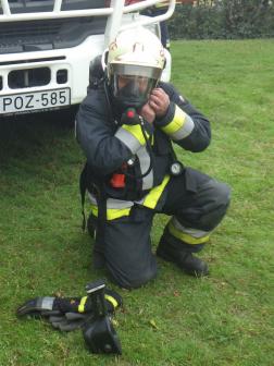 Sisakot csatol be a légzőálarcban lévő tűzoltó