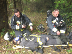Tűzoltók légzőkben és hordágyon a kimentett ember